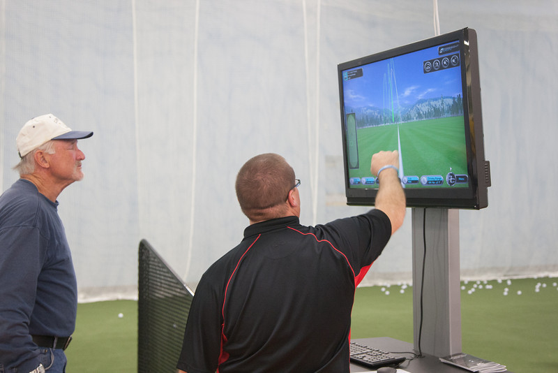 A manager at the newly opened Golfsmith goes over the computer's analasys of a customer's performance at their indoor driving range.