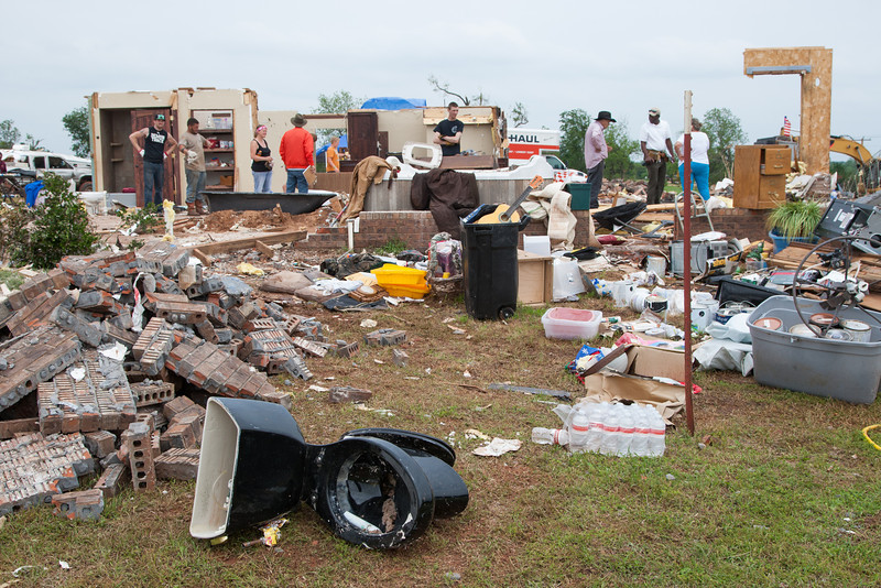 Residents of Carney cleaning up a niehbors property after their house was destroyed by an EF4 tornando on May 19, 2013.