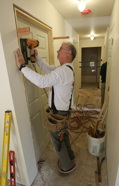 A volunteer installs a door in one of several Habitat for Humanity houses under construction in west Tulsa.