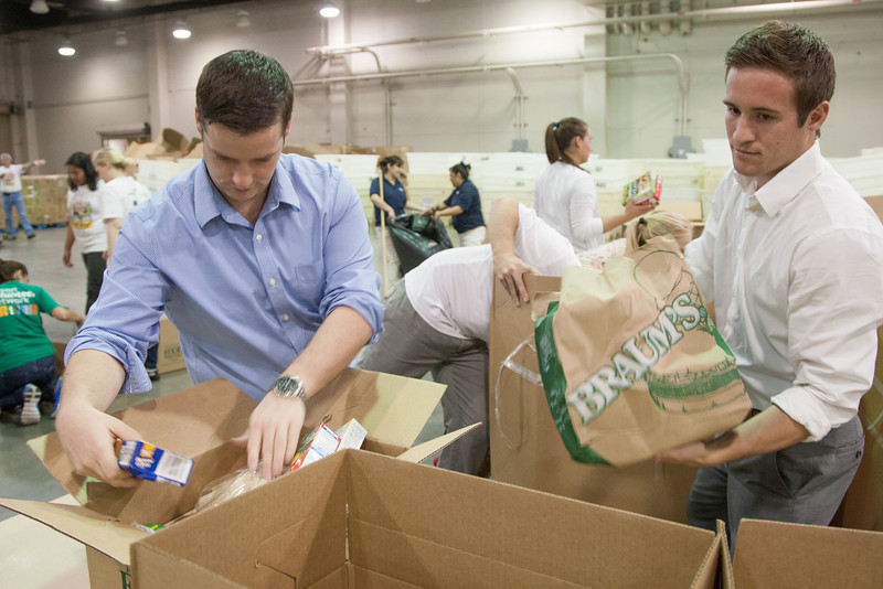Devon Energy employees Will Cain and Caleb Randell sort food for Feed the Children at the Cox Center.