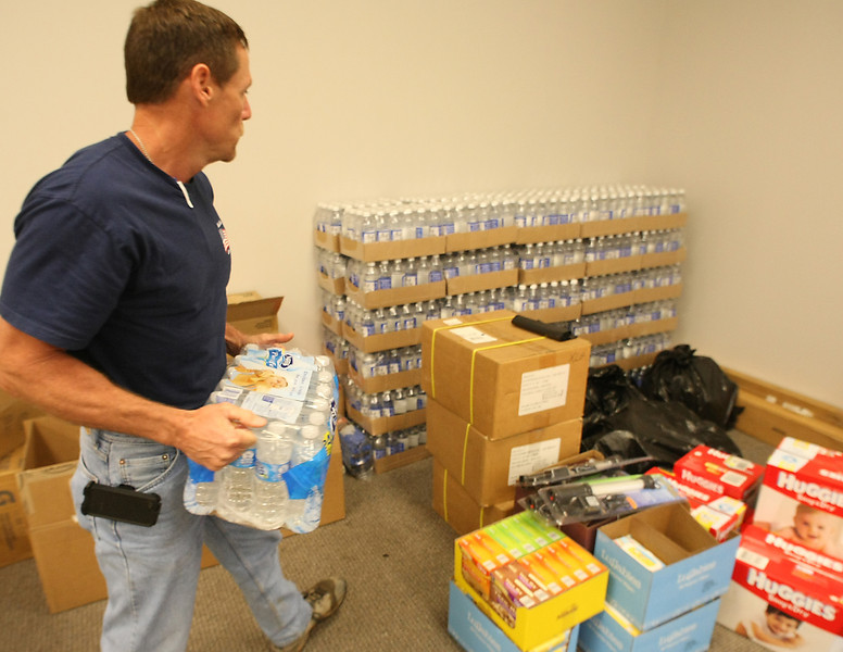 Dan Longshore, General Superintendent at Nabholz Construction stacks relief supplies collected for Moore and Shawnee tornado victims.