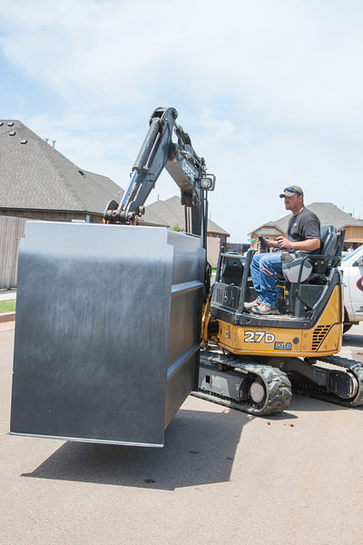Installers from Ground Zero Shelters install a large metal storm shelter at a home in Edmond, OK.