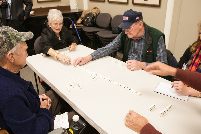 Gen Rita Aragon plays dominos with Oklahoma vets in the governer's conferance room.