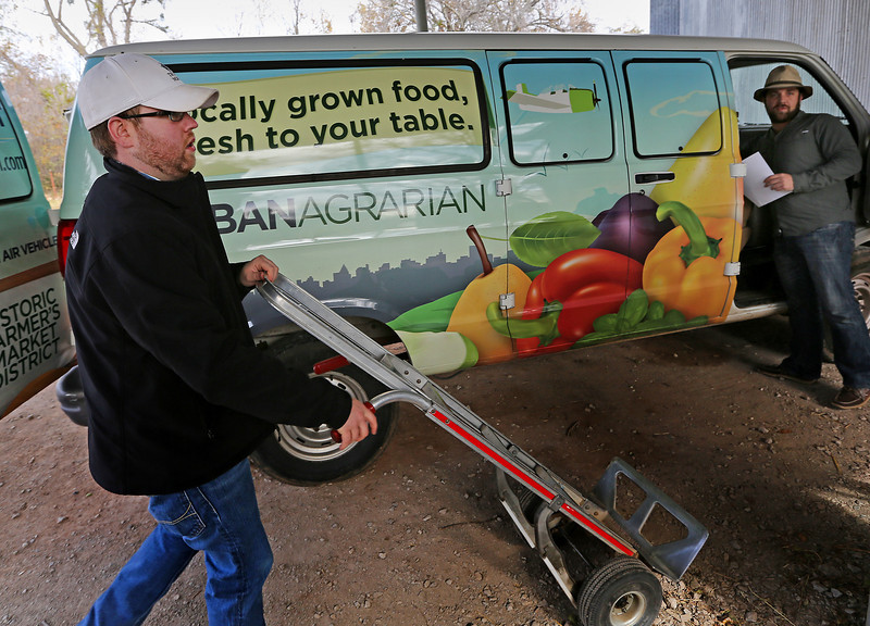 John Elliott of the A Good Egg Dining Group  and Matt Birch or Urban Agrarian Market load fresh produce from a Bixby farm.