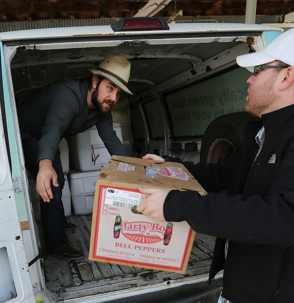 Matt Birch or Urban Agrarian Market and John Elliott of the A Good Egg Dining Group load fresh produce from a Bixby farm.