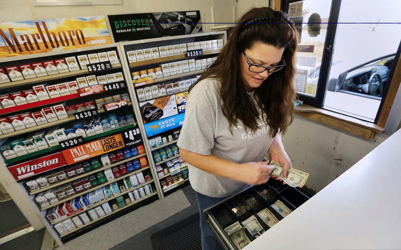 Toni Hall, clerk at the tribal smoke shop Smoke Signals of Tulsa, sell a pack of cigarettes to a customer Thursday. Tribal leaders and Republican Governor Mary Fallin are working to finalize agreements over tobacco sales. The tribes pay a fee to the state instead of taxes.