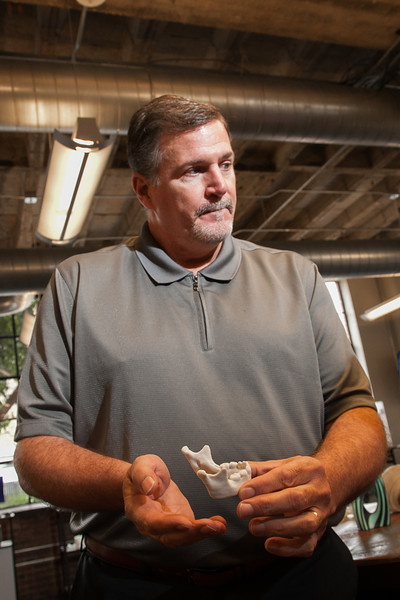 Brian Peltier, with Standley Systems, holding a 3D printed jaw bone.