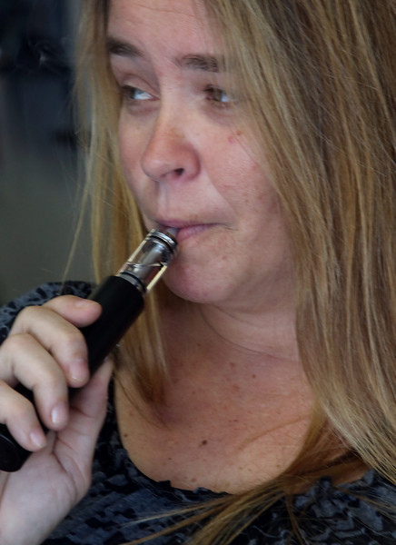 Kimberly Franks a salesman at Enigma Vapor in Tulsa uses her vaporer.  Franks uses the vaporizer as a replacement for cigarettes and to curb cravings for sweets.