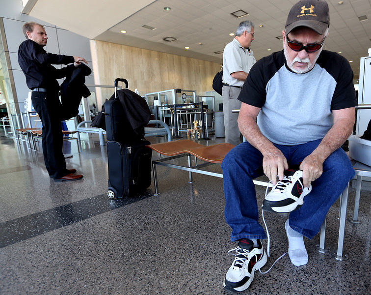 Billy Warren puts his shoes back on after going through the TSA security screening at the Tulsa International Airport.  TSA will offer a way to avoid this nuisance with the new TSA Pre-Check line which allows passengers to keep their shoes on and other perks.