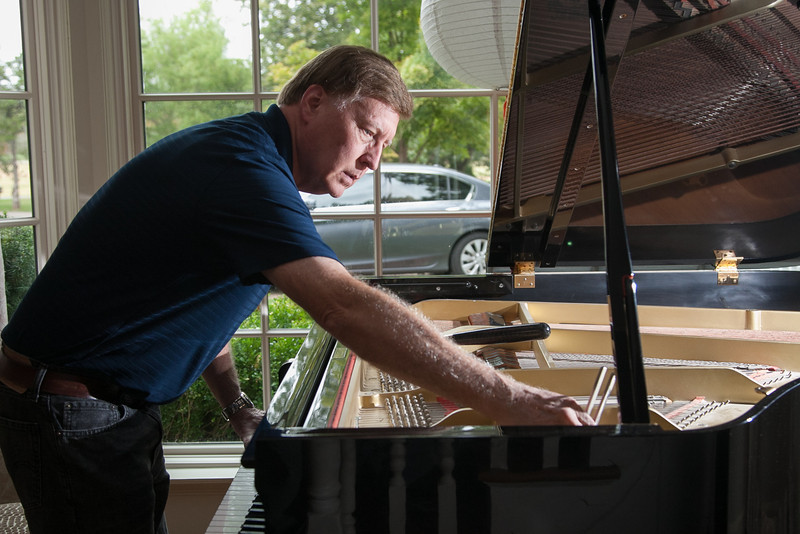 Steve Evens tunes a piano by ear at a home in Nichols Hills.