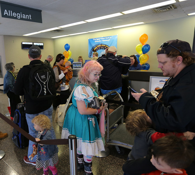 Kristi Roe-Owen and family check in at the Allegiant Airlines desk for their trip to Orlando Florida.
