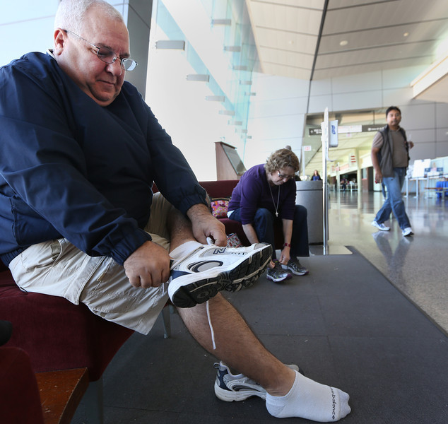 Kurt Kling puts his shoes back on after going through the TSA security screening at the Tulsa International Airport.  TSA will offer a way to avoid this nuisance with the new TSA Pre-Check line which allows passengers to keep their shoes on and other perks.