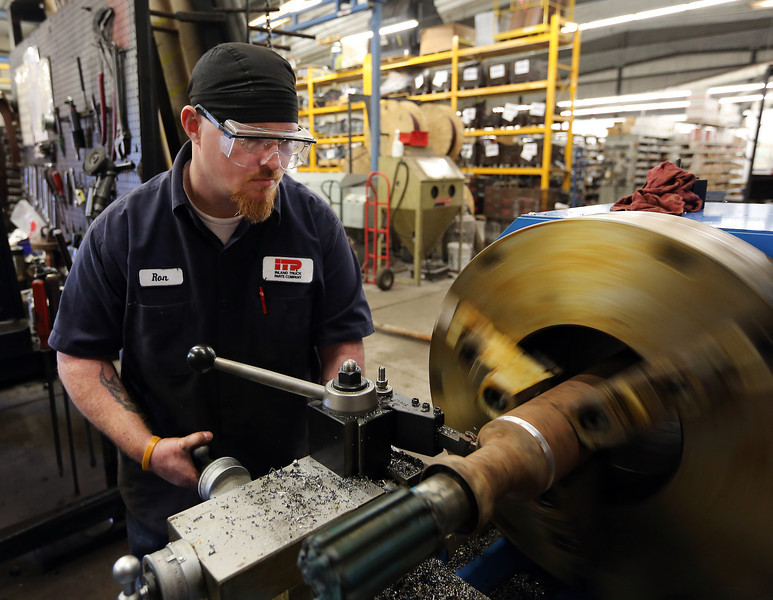 Ron Greene, Drive Line Technician, turns a shaft on a lathe at Inland Truck Parts Company in Tulsa.