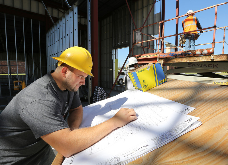 Electrician Anthony Yeargain goes over plans at the Grand Bank construction site in South Tulsa.