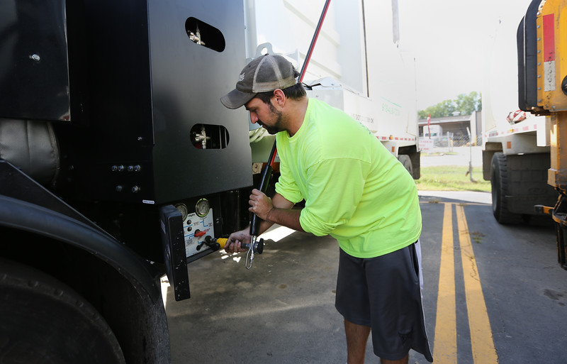 Mike Almy attaches the filling hose to his truck at the CNG filling station at the NeWSolutions yard in Tulsa.