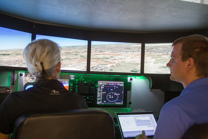 Pilot Katie Robertson flying in Oklahoma Aviation's new 3 axis flight simulator with flight instructor Ross Fischer.