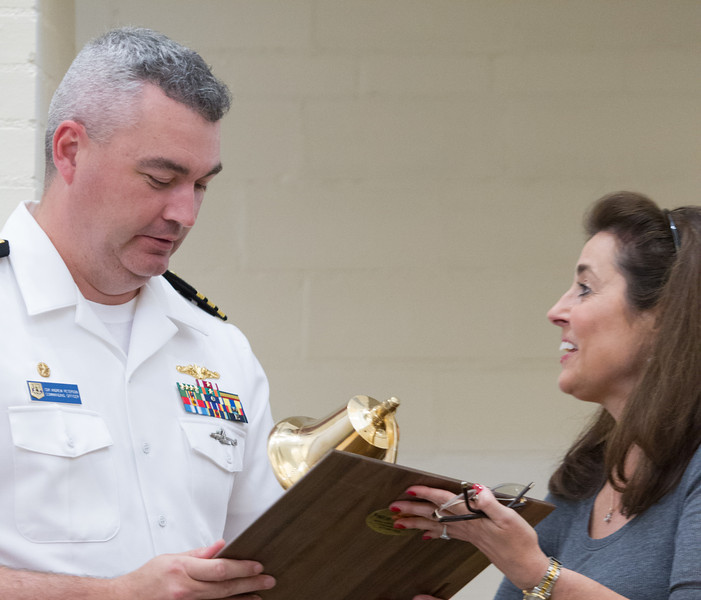 Debbie Hampton, president of United Way of Central Oklahoma, presents Andrew Peterson commanding officer of the USS Oklahoma City, a navy bell. The crew of the Oklahoma City raised money for storm relief and presented a check to the United Way.