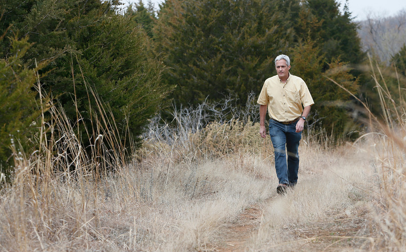 Oklahoma State University Professor of Natural Resource Ecology and Management Rodney Will walks through a stand of red cedar trees he studies.