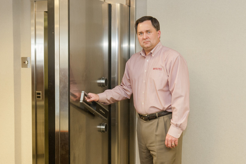 Brent Taylor, President and CEO of WEOKIE Credit Union, standing next to the vault door at the bank's main office. After modifying the door the vault can serve as a storm shelter.