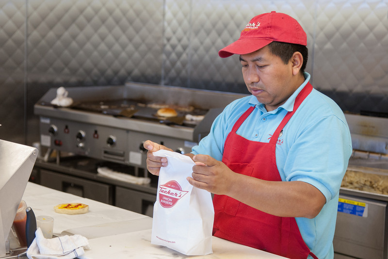 Manuel Huinac prepares burger orders at Tucker's Onion Burgers at Classen Curve in Oklahoma CIty, OK.