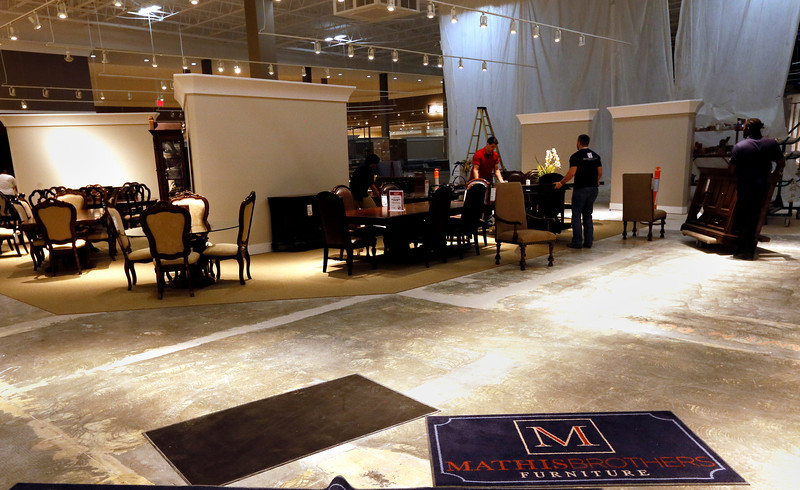 Employees move furniture into the remodeled Tulsa display area.
