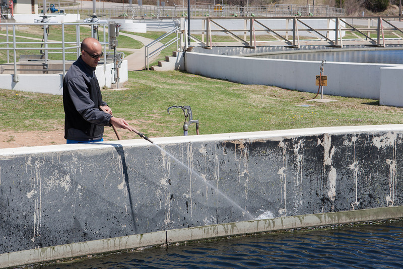Ryan Bart, with the City of Norman, cleans a sewage treatment tank using re-use water that has been cleaned by the Water Reclamation Facility.