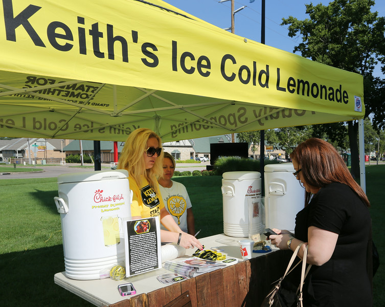 Melanie Lemons gives a glass of Keith's lemonade to Dana Davis.