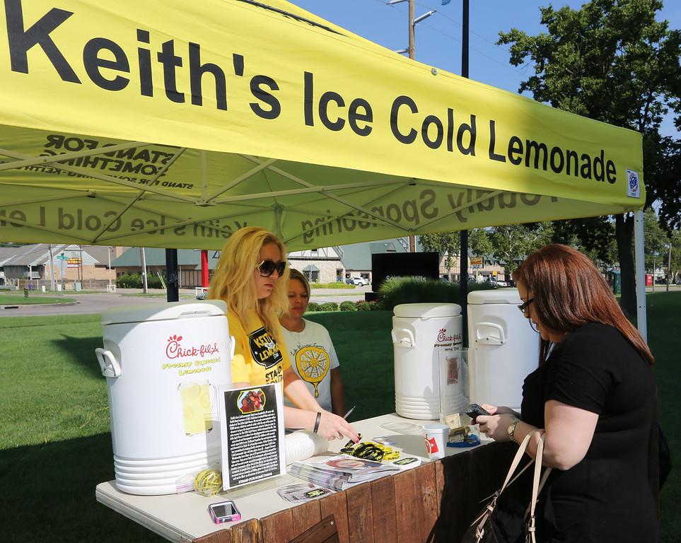 Melanie Lemons gives a glass of Keith's lemonade to Dana Davis.
