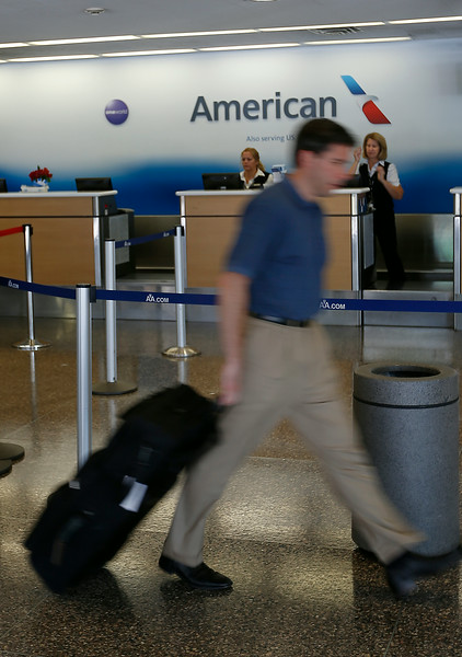 A traveler walks past the American Airlines counter at Tulsa International Airport.  Passenger traffic at Tulsa International Airport  was up more than 13 percent in July compared to last year.