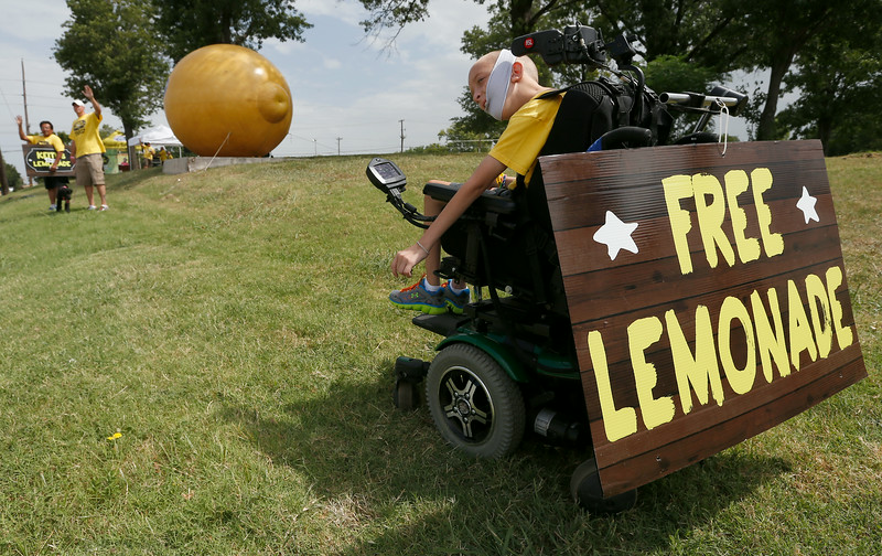 Keith Boyd uses a sign taped to the back of his wheel chair to advertise his lemonade stand.  Any money raised at the stand goes to the Little Lighthouse in Tulsa.<br /> <br /> 10-year-old entrepreneur Keith Boyd finished out this summer's Keith's Ice Cold Lemonade Stand fundraising efforts Wednesday at Tulsa's Little Lighthouse, provider of educational and therapeutic services to special-needs children and beneficiary of Boyd's project. He will present that nonprofit a $120,000-plus check during a 7 p.m. Friday celebration at Riverwalk Crossing in Jenks. Boyd's family and supporters also will launch a $50,000 Kickstarter campaign Friday to fund the nonprofit startup manufacturer Keith's Ice Cold Beverages. This Tulsa firm intends to sell Keith's Ice Cold Lemonade in bottles and juice boxes at stores across Oklahoma, with the profits going to Boyd's new Tulsa nonprofit benefitting the needy and their support organizations.