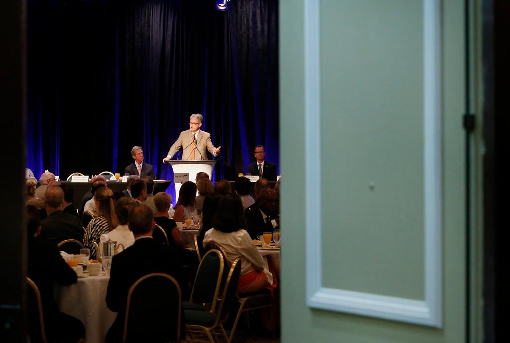 Seen through an open door at the Hyatt Hotel in Tulsa Oklahoma Senator Tom Coburn gives his presentation at the Congressional Forum Breakfast.