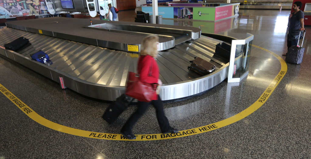 Travelers wait for their bags at the Tulsa International Airport.  Passenger traffic at Tulsa International Airport  was up more than 13 percent in July compared to last year.