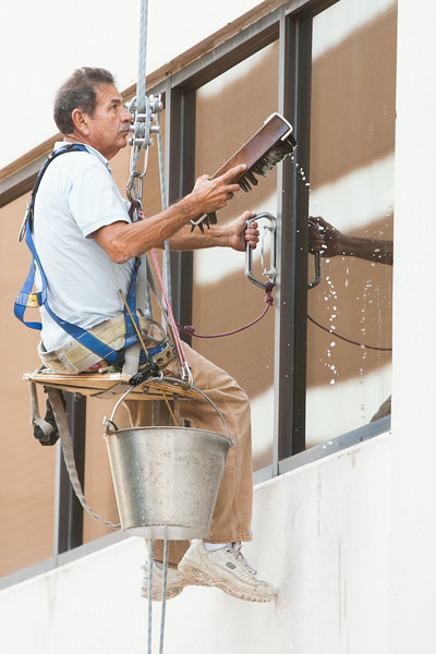 A man cleaning windows while dangling off the side of the BancFirst Building in downtown Oklahoma City, OK.