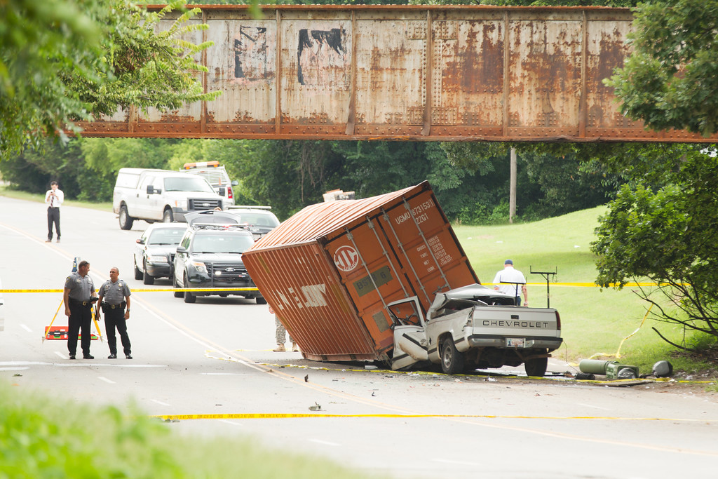 A cargo container being carried on an Oklahoma National Guard truck hit a bridge and fell onto an oncoming pickup truck. The driver of the smaller truck died at the scene.