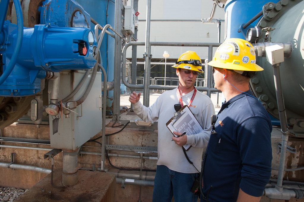Donnie Jackson, auxiliary operator (gray shirt), and Grant Craft, shift supervisor (blue shirt) with OG&E Electric Services, talk about power plant equipment during daily rounds at the Redbud power plant near Arcadia.