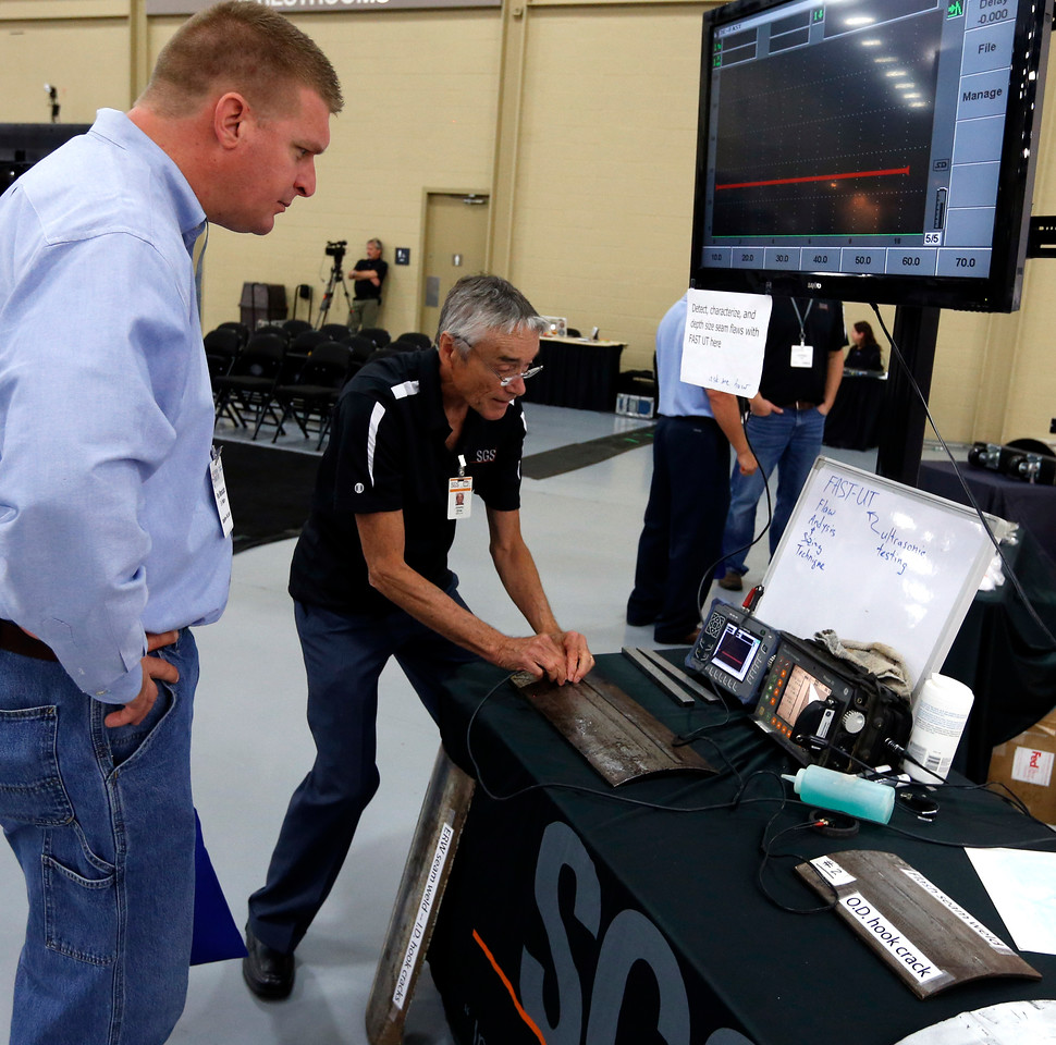 Jimmy Ellis of SGS Pfinde Inc. demonstrates to an attendee of the Pipeline Expo in Tulsa, one of the tools<br /> the company  uses to provide pipe inspection services.