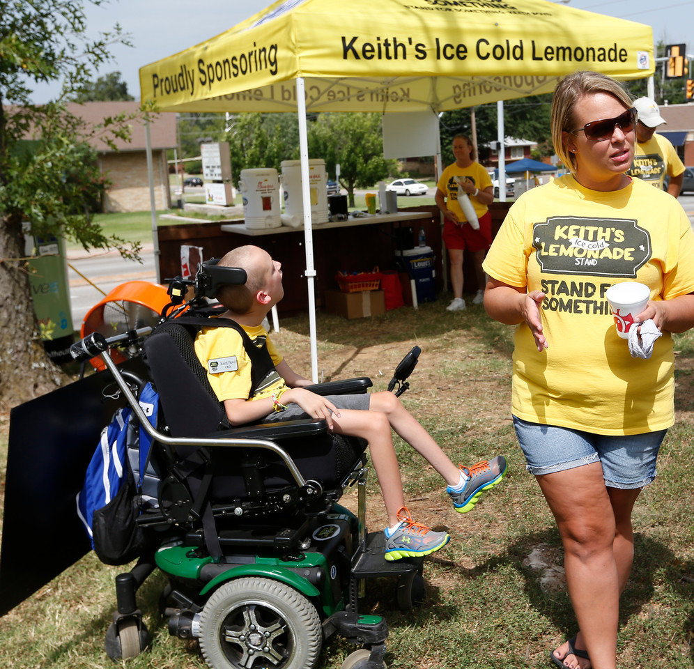 Stuart Walling of Lawn America waves at passing motorists at the Keiths Lemonade stand in mid-town Tulsa.