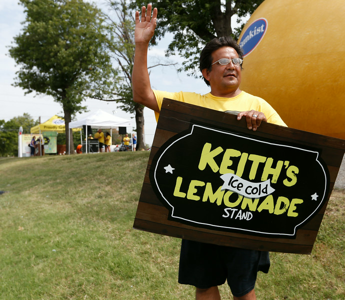 Stuart Walling of Lawn America waves at passing motorists at the Keiths Lemonade stand in mid-town Tulsa.<br /> <br /> 10-year-old entrepreneur Keith Boyd finished out this summer's Keith's Ice Cold Lemonade Stand fundraising efforts Wednesday at Tulsa's Little Lighthouse, provider of educational and therapeutic services to special-needs children and beneficiary of Boyd's project. He will present that nonprofit a $120,000-plus check during a 7 p.m. Friday celebration at Riverwalk Crossing in Jenks. Boyd's family and supporters also will launch a $50,000 Kickstarter campaign Friday to fund the nonprofit startup manufacturer Keith's Ice Cold Beverages. This Tulsa firm intends to sell Keith's Ice Cold Lemonade in bottles and juice boxes at stores across Oklahoma, with the profits going to Boyd's new Tulsa nonprofit benefitting the needy and their support organizations.