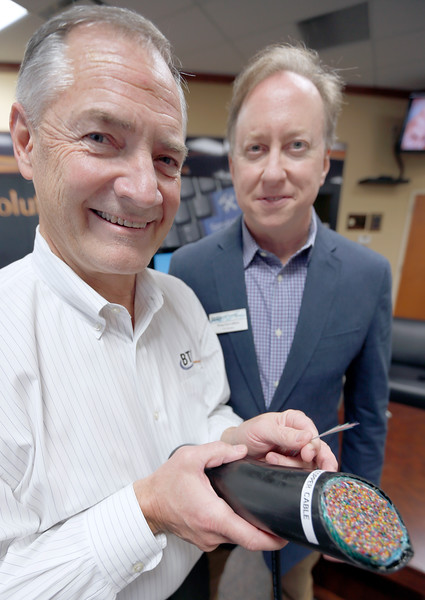Scott Floyd, President of Bixby Telephone Company and Douglas Enevoldsen, City Manager for Bixby, demonstrate the different cables carrying internet traffic enabling Bixby to become a Gigabit City  One strand of the fiber optic cable carries more data than the entire copper cable.
