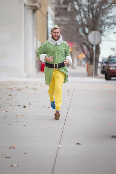 Griffin Radford running in his elf costum in fron of Sandridge Energy.