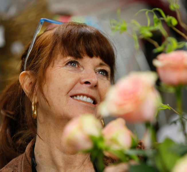 Sandy Snow of Stems flower shop in Tulsa's Utica Square Shopping Center arranges a flower bouquet for valentines.