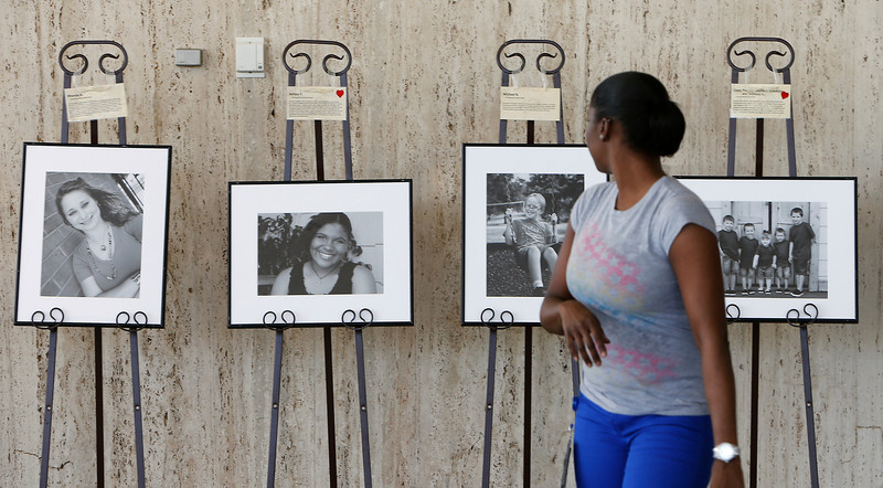 Regina Hatcher checks her work after setting up photographs for the Waiting Child Heart Gallery display at the Tulsa International Airport.  The Heart Gallery is a traveling photographic  exhibit created to find adoptive families for children in foster care.