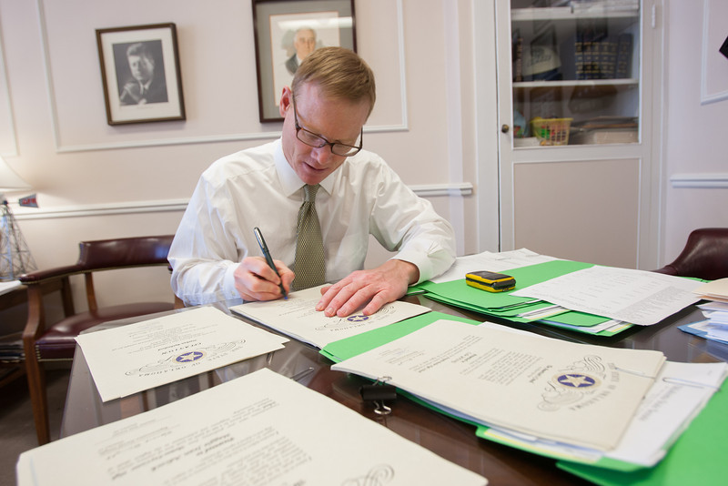 Oklahoma Sen. Tom Ivester signs certificates for high school graduates in his office at the Oklahoma State Capitol.