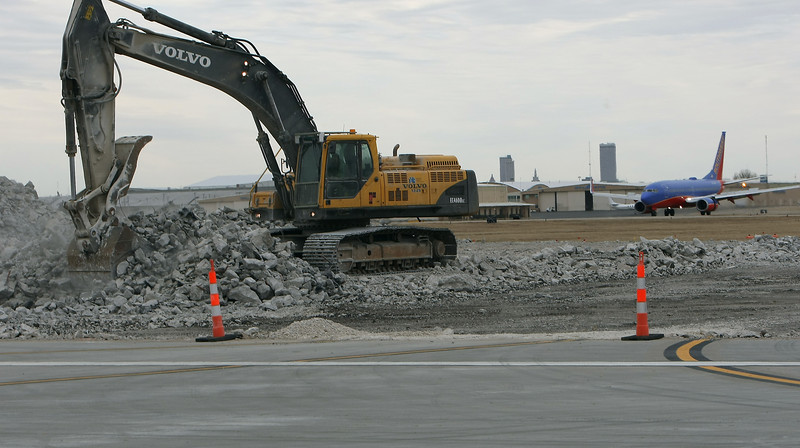 Workmen use a backhoe to help remove part of the main runway at Tulsa International Airport.