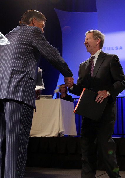 The Tulsa Regional Chamber 2013 Chair Jake Henry Jr.  congratulates his successor Wade Edmundson, CEO of Commerce Bank, as the 2014 Chairman of the Board of Directors.