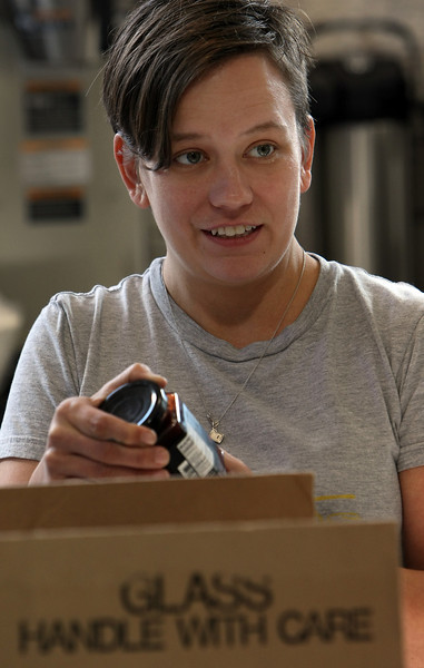 Ali Wokoun inspects arriving products as she works to get the Folks Urban Market and Pantry in downtown Tulsa ready for their Friday grand opening.