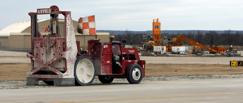 A concrete buster works to break up part of the main runway at Tulsa International Airport.