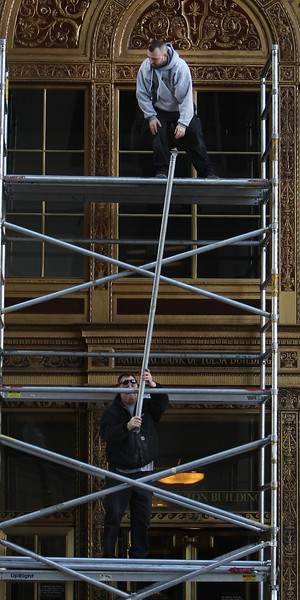 Workmen disassemble scaffolding outside the 320 S Boston Building in downtown Tulsa.