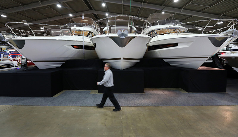 A vendor walks by a few of the many boats on display at the Tulsa Boat Sport & Travel Show.