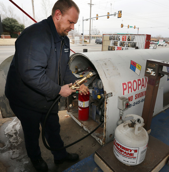 Nick Mancino refills a propane cylinder at the American Discount Brake and Muffler shop in Tulsa.  Propane prices are nearly double what they were last winter.